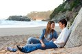 Young handsome couple sitting on beach. Royalty Free Stock Photos