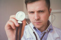 Young handsome doctor holding stethoscope Royalty Free Stock Photo