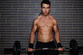 Young handsome guy weightlifter lifting barbell exercising chest and biceps muscle at gym Royalty Free Stock Photo