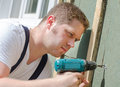 Young handsome handyman using screwdriver Stock Photo