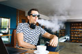 Young handsome hipster man insunglasse sitting in cafe with a cup of coffee, vaping and releases a cloud of vapor Royalty Free Stock Photo