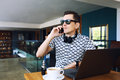 Young handsome hipster man in sunglases sitting in cafe talking mobile phone. Laptop on wooden table. Royalty Free Stock Photo