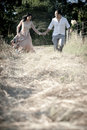 Young handsome indian laughing couple running in field with white roses and Stock Photos