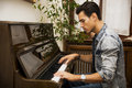 Young handsome male artist playing classical upright piano Royalty Free Stock Photo