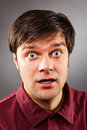 Young handsome man with astonished expression isolated on gray background Royalty Free Stock Photo