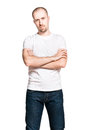 Young handsome man with folded arms in white t shirt vertical portrait of a and blue jeans isolated on Stock Photography