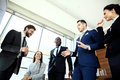 Young handsome man gesturing and discussing something while his coworkers listening to him at the office Royalty Free Stock Photo