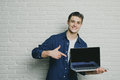 Young handsome man point the finger at a blank screen laptop, looking at the camera, happy smile, against a brick wall Royalty Free Stock Photo