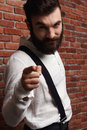 Young handsome man pointing finger at camera over brick background. Royalty Free Stock Photo