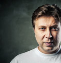 Young handsome man with serious expression on dark Royalty Free Stock Photo