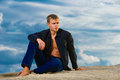 Young handsome man is sitting on the sand on the beach. Looks th Royalty Free Stock Photo