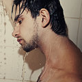 Young handsome man takes a shower closeup portrait of Royalty Free Stock Image