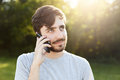 Young handsome man with thick beard and dark big eyes holding smart phone phoning his friend while standing at green background. H Royalty Free Stock Photo