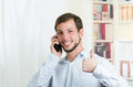 Young handsome man using cell phone talking looking happy holding thumb up Royalty Free Stock Photo