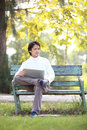 A young handsome man using laptop sitting on a ben bench looking in park green bench Stock Photos