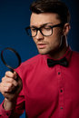 Young handsome man wearing fashion eyeglasses look through a magnifying glass Royalty Free Stock Photo