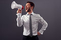 Young handsome shouting man using megaphone over grey background Royalty Free Stock Photo