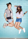Young happiness women two are jumping against blue wall lifestyle Stock Photos