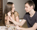 Young happy amorous couple celebrating with white wine at restaurant holding hand Stock Image