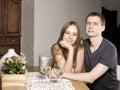 Young happy amorous couple celebrating with white wine at restaurant holding hand Stock Image