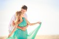 Young happy asian couple on honeymoon handsome men hold his beautiful blonde girlfriend in blue dress Royalty Free Stock Images