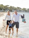 Young happy beautiful family playing together on the beach enjoying summer holidays Royalty Free Stock Photo