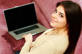 Young happy beautiful woman sitting on the sofa with laptop at home Royalty Free Stock Image