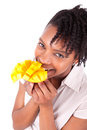Young happy black african american woman eating fresh mango isolated on white background Royalty Free Stock Image