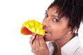 Young happy black african american woman eating fresh mango isolated on white background Stock Photography