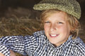 Young happy blond boy child plaid shirt flat cap smiling aged about or early teenager wearing a and sitting on hay or straw bales Stock Image