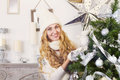 Young happy blond woman near the Christmas tree Royalty Free Stock Photo