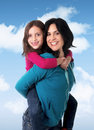 Young happy brazilian mother carrying on her back little daughter having fun together smiling posing a blue sky with clouds in Royalty Free Stock Photo