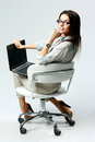 Young happy businesswoman sitting on the office chair with laptop Royalty Free Stock Image