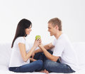 A young and happy caucasian couple waiting for the baby and eating healthy food in jeans the image is isolated on a white Royalty Free Stock Images