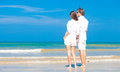 Young happy caucasian couple in white standing on beach looking at the sea this image has attached release Stock Photos