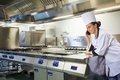 Young happy chef standing next to work surface phoning in professional kitchen Royalty Free Stock Photography