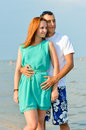 Young happy couple embracing on sandy beach beautiful women handsome men Stock Image