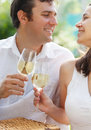 Young happy couple enjoying a glasses of white wine Stock Photography