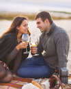 Young happy couple enjoying picnic on the beach together Stock Photo