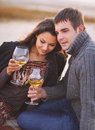 Young happy couple enjoying picnic with white wine on the beach together Royalty Free Stock Photography