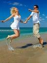 Young happy couple having fun on sea beach Stock Photos
