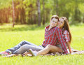 Young happy couple having fun in summer sitting on the grass joyful pretty girl and men resting the park Royalty Free Stock Image