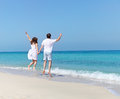 Young happy couple jumping on the beach holding hands Royalty Free Stock Photography