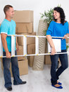 Young happy couple with a ladder in his hands in new home boxes apartment Royalty Free Stock Images