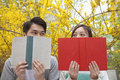 Young happy couple looking at each other over the top of their books outdoors in spring Stock Image