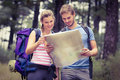 Young happy couple looking at a map in the nature Royalty Free Stock Image