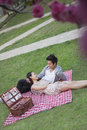 Young happy couple lying on a blanket together while having a picnic in the park blossoms in the foreground Stock Images