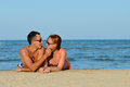 Young happy couple man and woman lying on sandy beach men women having fun Stock Photo