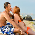 Young happy couple man and woman lying on sandy beach men women kissing Royalty Free Stock Photography