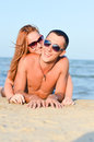 Young happy couple man and woman lying on sandy beach smiling embracing summer sea background Stock Photos